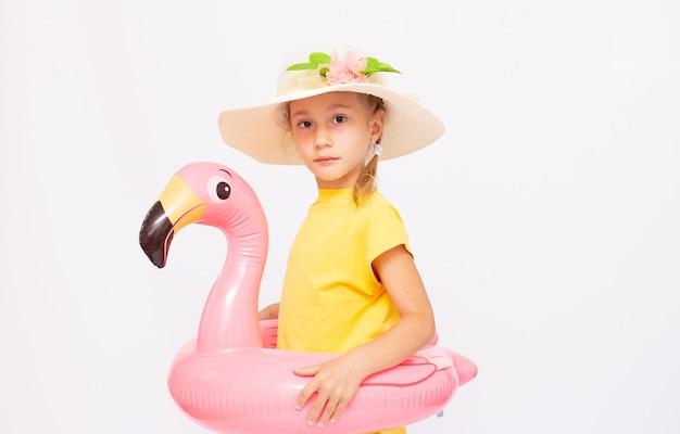 Modelo infantil, superfície branca, menina em traje de banho com flamingo inflável
