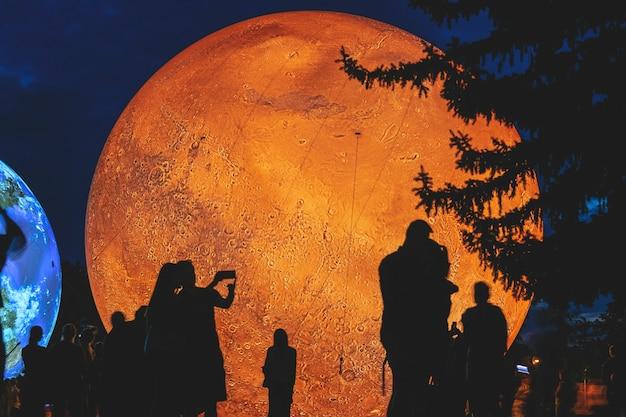 Modelo inflável gigante do planeta marte à noite com silhuetas de pessoas. superfície do planeta vermelho marte. colonização de marte.