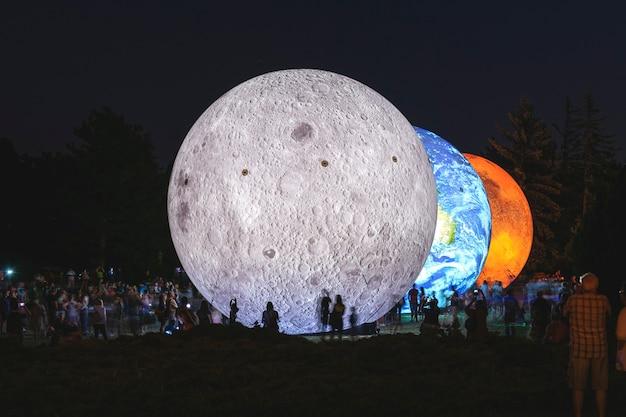 Modelo inflável gigante dos planetas marte, terra e lua à noite com silhuetas de pessoas. pesquisa do sistema solar.