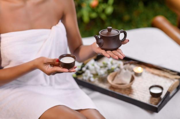 Modelo interracial posando segurando um bule de barro em uma mão enquanto de repente uma pequena xícara de barro