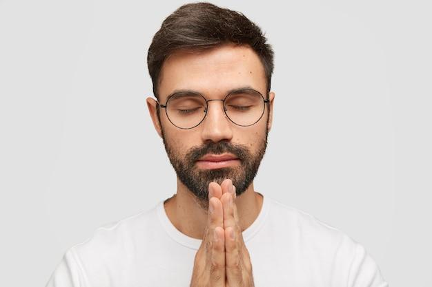 Modelo jovem barbudo focado mantém as palmas das mãos em gesto de oração, acredita na boa sorte.
