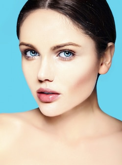 Modelo jovem caucasiano com maquiagem nude, tocando sua pele limpa perfeita em azul