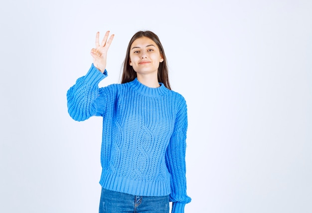 Modelo jovem de suéter azul, mostrando o número três em branco-cinza.