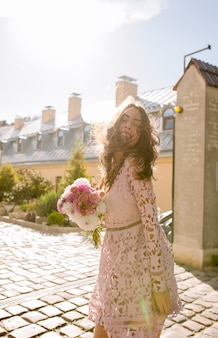 Modelo jovem e atraente com vestido de renda rosa, posando para raios de luz pela manhã
