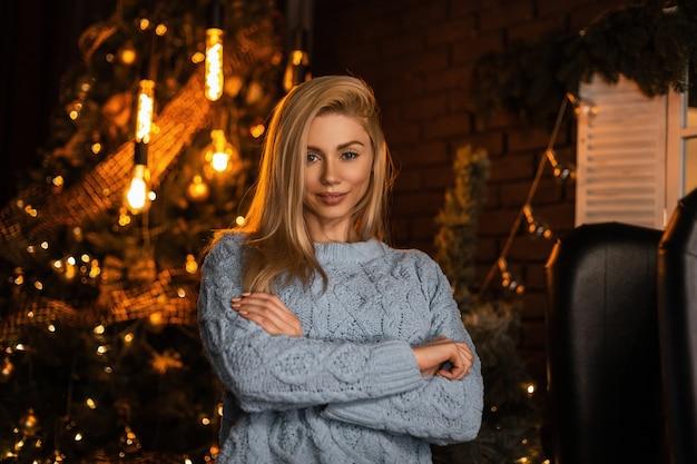 Modelo jovem e sexy e feliz de uma linda mulher loira com um suéter de malha elegante posando em um quarto escuro contra uma árvore de natal festiva e brilhante com guirlandas vintage