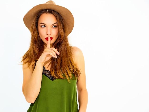 Modelo jovem elegante em roupas casuais de verão verde e chapéu marrom com lábios vermelhos, mostrando o gesto de silêncio com o dedo, isolado