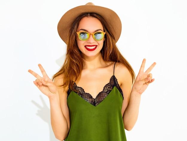 Modelo jovem elegante em roupas casuais de verão verde e chapéu marrom com lábios vermelhos, mostrando sinal de paz