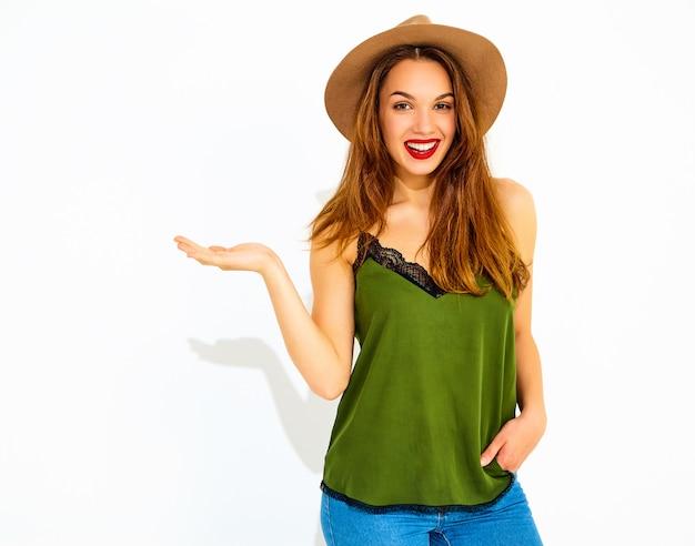 Modelo jovem elegante em roupas casuais de verão verde e chapéu marrom com lábios vermelhos, segurando algo na mão, isolado