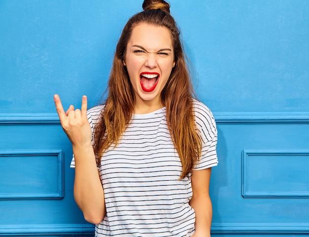 Modelo jovem elegante em roupas de verão casual com lábios vermelhos, posando perto da parede azul. gritando e mostrando sinal de rock and roll