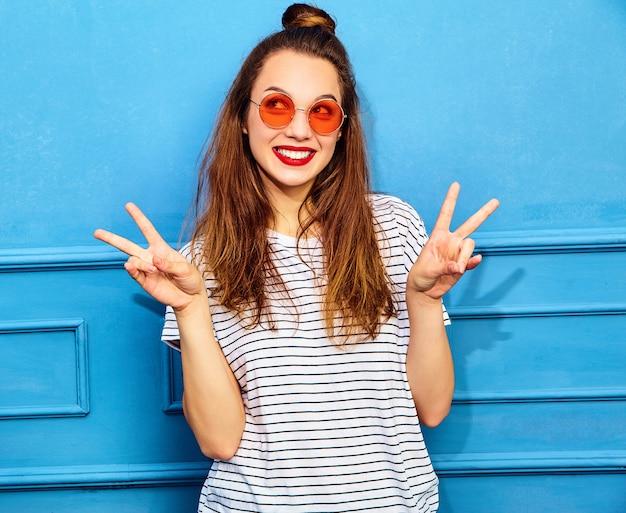 Modelo jovem elegante em roupas de verão casual com lábios vermelhos, posando perto da parede azul. mostrando sinal de paz