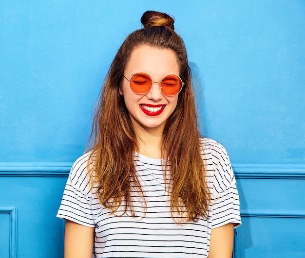 Modelo jovem elegante em roupas de verão casual com lábios vermelhos, posando perto da parede azul. olhos felizes e fechados