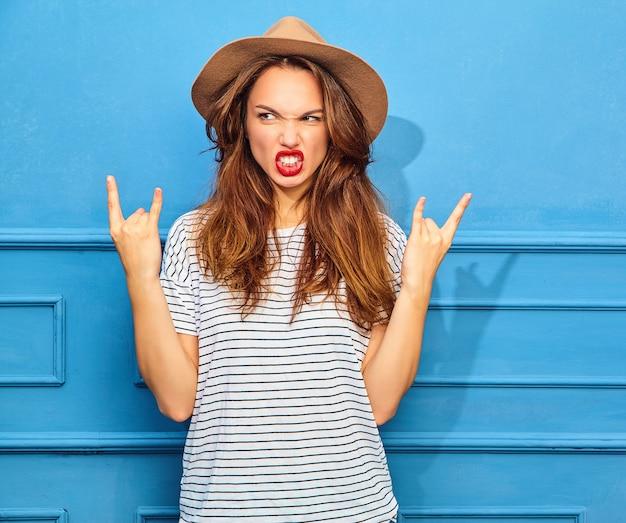 Modelo jovem elegante em roupas de verão casual e chapéu marrom com lábios vermelhos, posando perto da parede azul. mostrando sinal de rock and roll