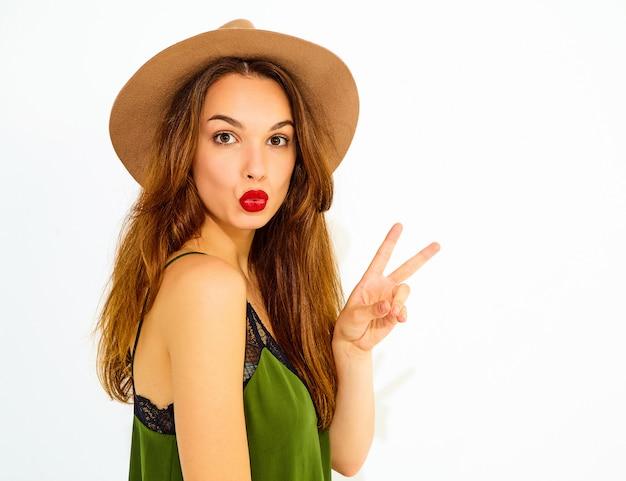 Modelo jovem elegante em roupas de verão casual verde e chapéu marrom com lábios vermelhos. mostrando sinal de paz e dando beijo