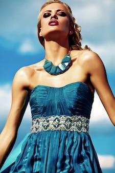 Modelo jovem mulher loira sexy vestido de noite posando no fundo do céu azul