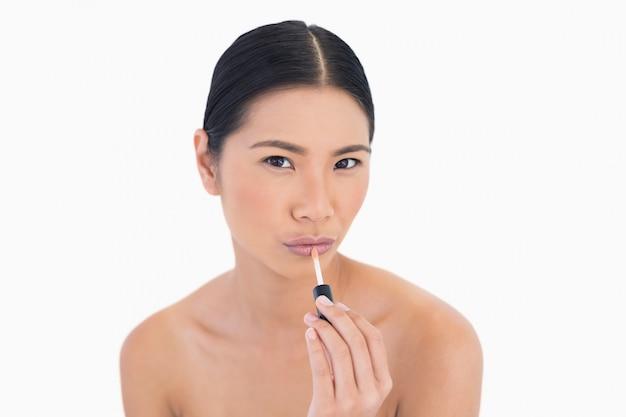 Modelo jovem sensual aplicando brilho labial