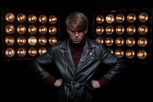 Modelo jovem sério em uma jaqueta de couro elegante no estilo do rock and roll, posando e olhando para a câmera na sala, contra o pano de fundo de lâmpadas vintage laranja profissionais brilhantes.