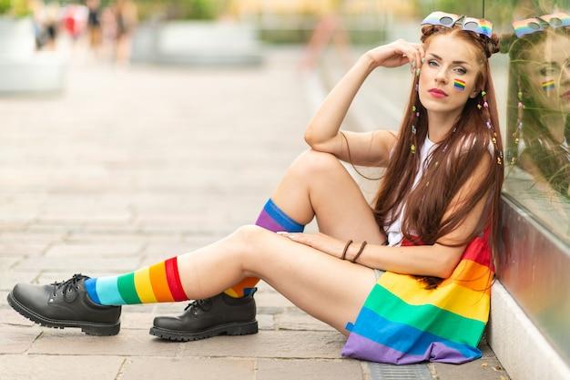 Modelo lésbica elegante com bandeira lgbt no rosto posando ao ar livre.