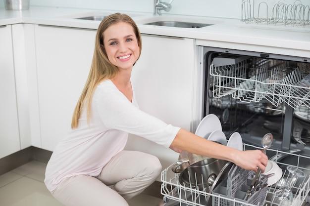 Modelo lindo alegre ajoelhado ao lado da máquina de lavar louça