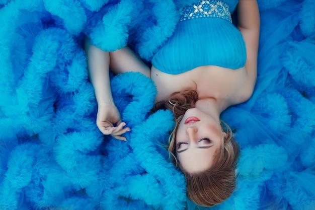 Modelo lindo em um vestido azul sobre neutro