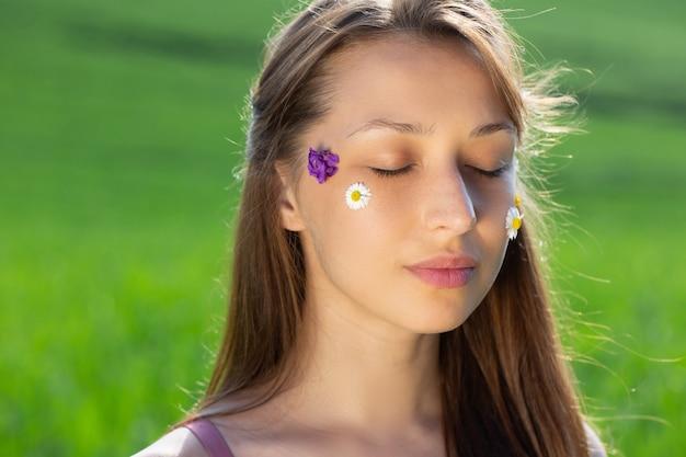 Modelo lindo posando de olhos fechados com flores silvestres no rosto em um campo verde borrado