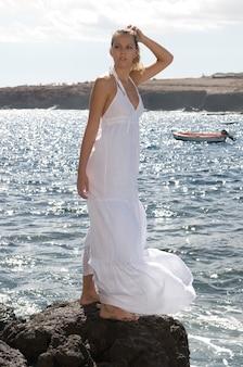 Modelo loira atraente em uma vila de pescadores à beira-mar