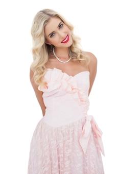 Modelo loira feliz em vestido rosa posando olhando