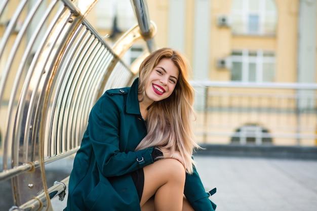Modelo loira feliz vestindo um casaco verde, posando para a rua. espaço para texto