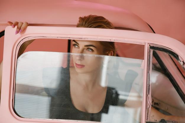 Modelo loira olhando para fora do carro vintage rosa. estilo de moda conceitual.