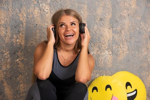 Modelo loira segurando fones de ouvido e ouvindo música e se divertindo.