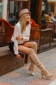 Modelo loira sexy bonita com blusa branca e skrt de couro e botas altas de malha em bege
