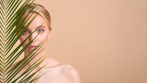 Modelo loiro close-up atrás de uma planta com cópia-espaço