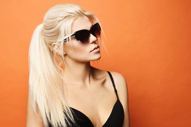 Modelo loiro com corpo perfeito em sutiã preto e óculos de sol na parede laranja