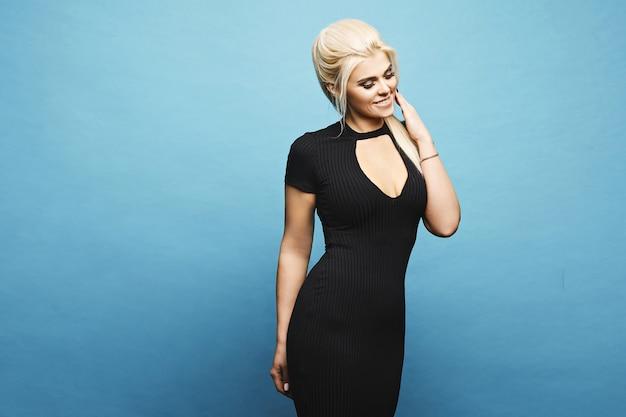 Modelo loiro com corpo perfeito em vestido preto apertado, posando na parede azul