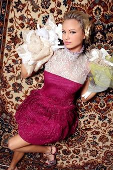 Modelo loiro de vestido rosa com detalhes de tule, deitado no chão