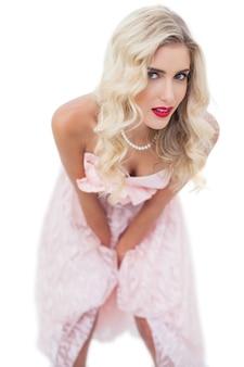 Modelo loiro e loiro com vestido rosa posando as mãos nas coxas