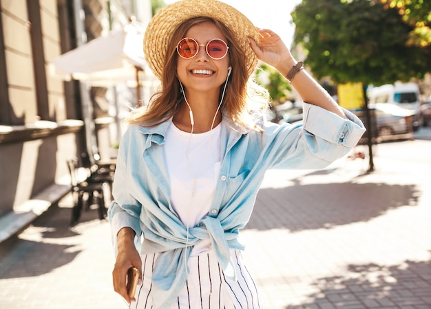 Modelo loiro em roupas de verão posando na rua