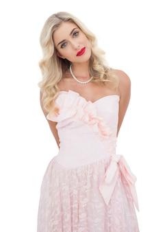 Modelo loiro satisfeito em vestido rosa posando olhando câmera