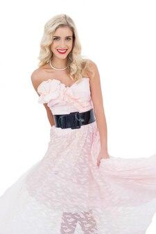 Modelo loiro satisfeito no vestido rosa posando agitando seu vestido