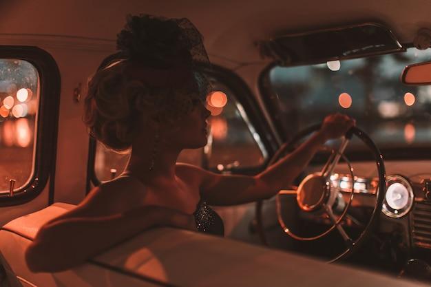 Modelo loiro sexy moda linda com maquiagem brilhante e penteado encaracolado em estilo retro, sentado no carro velho