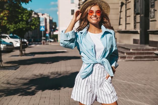 Modelo loiro sorridente em roupas de verão, posando na rua