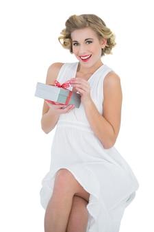 Modelo loura de moda encantada, abrindo um presente