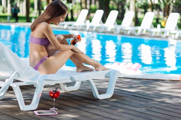 Modelo magro e atraente de sucesso passando seu tão esperado dia de folga perto de uma grande piscina externa