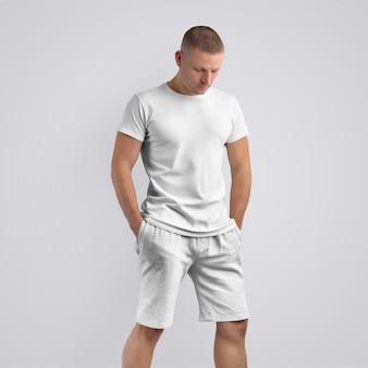 Modelo magro elegante em uma camiseta em branco e shorts cinza de malha em um fundo branco do estúdio. pose frontal. o modelo pode ser usado em seu design.