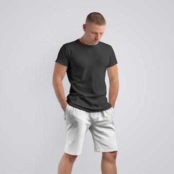 Modelo magro elegante em uma camiseta preta e shorts cinza de malha em um fundo branco do estúdio. pose frontal. o modelo pode ser usado em seu design.