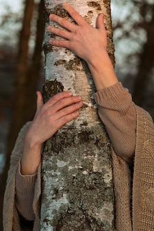 Modelo masculino abraçando uma árvore