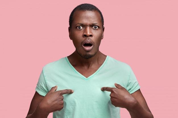 Modelo masculino afro-americano descontente e irritado indica uma camiseta para seu design ou logotipo, franze a testa e está insatisfeito com algo, isolado sobre rosa