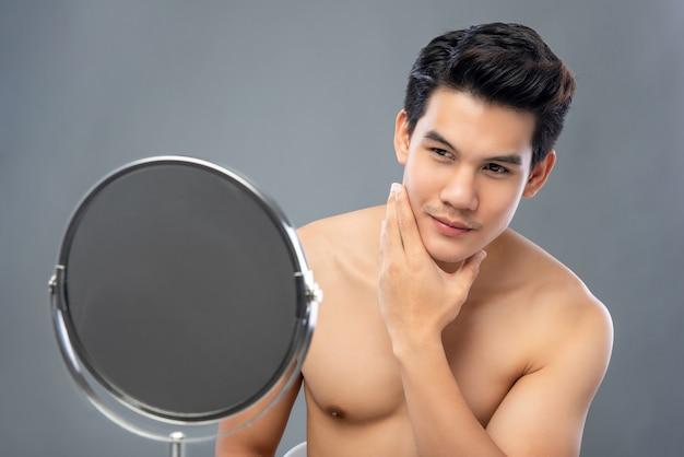 Modelo masculino asiático com confiança, olhando-se no espelho
