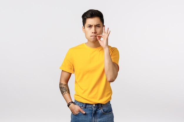 Modelo masculino asiático sério e determinado em t-shirt amarela, com tatuagens, chupar os lábios, boca fechada, fazendo um gesto perto dos lábios como se estivesse seguro e dizendo para não contar algo, mantenha segredo, conceito de silêncio