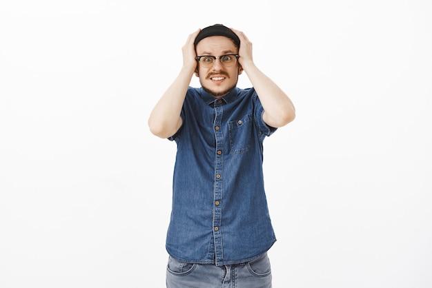 Modelo masculino atraente, nervoso e chocado com bigode no gorro e óculos segurando as mãos na cabeça cerrando os dentes e olhando ansioso em pânico lembrando que esqueceu de desligar o ferro