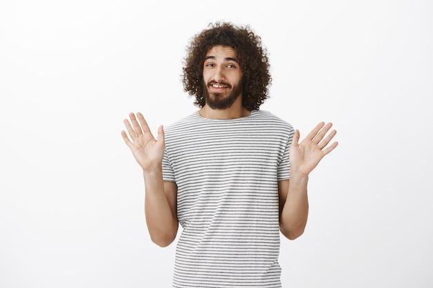 Modelo masculino bonito descuidado com penteado afro e barba doentia, levantando as mãos em sinal de rendição e sorrindo nervosamente